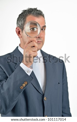 Businessman in a suit looking through a magnifying glass. Isolated on white - stock photo