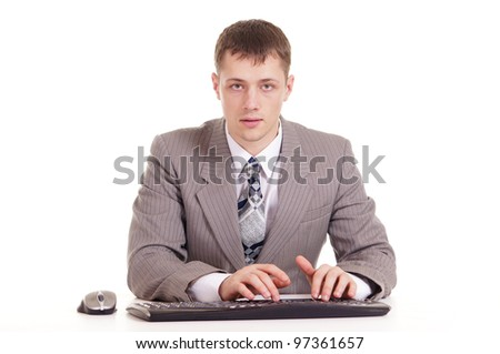 businessman in a suit sitting at a laptop on a background