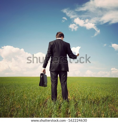 businessman in a suit standing on a green field with a blue sky and reads the newspaper or documents