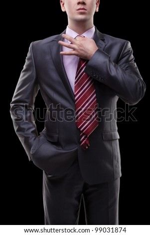 Businessman in a suit straightens his tie. - stock photo