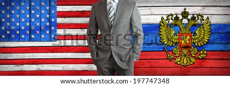 Businessman in a suit. USA and Russian flags as background. Concept of business - stock photo