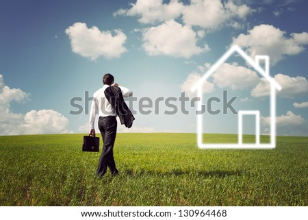 businessman in a suit with a briefcase goes to the house to a spacious green field with a blue sky - stock photo