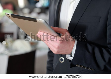 businessman in a suit with a clipboard in his hand in the restaurant