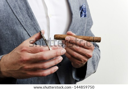 Businessman in a suit with blue handkerchief cutting cigare - stock photo