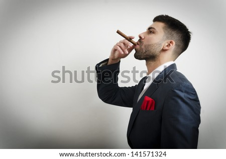Businessman in a suit with red handkerchief smoking cigar - stock photo