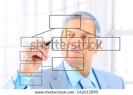 Businessman in age, draws a graph. Isolated on a white background.