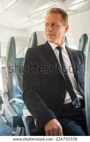 Businessman in airplane. Confident mature businessman sitting at his seat in airplane