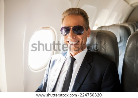 Businessman in airplane. Confident mature businessman sitting at his seat in airplane and smiling - stock photo