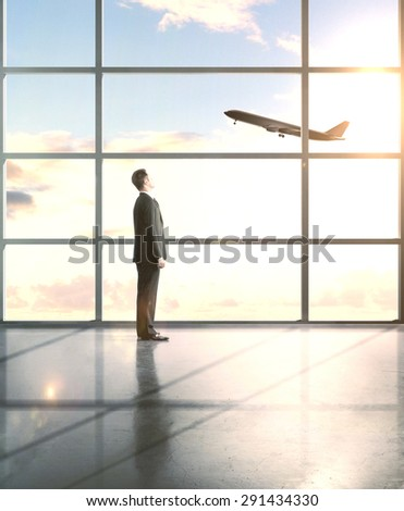 businessman in airport looking to airplane in sky - stock photo