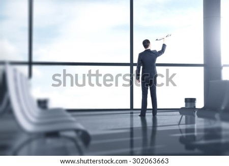 businessman in airport with airplane in hand