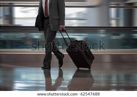 Businessman in airport with suitcase. - stock photo