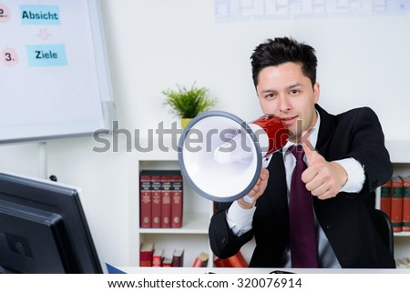 businessman in an office, shouting on a megaphone, shows thumb up