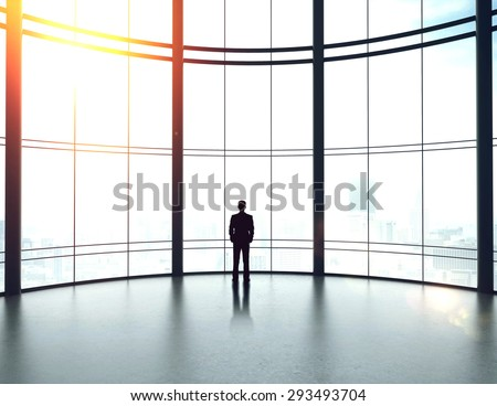 businessman in big sunlight office looking to window - stock photo