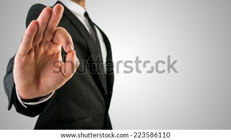 Businessman in Black Coat Showing Okay Hand Gesture. Isolated on Gradient Gray Sky Background. - stock photo