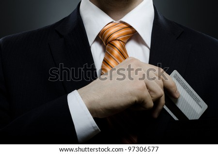 businessman in black costume and orange necktie put or take out credit card in pocket, close up - stock photo