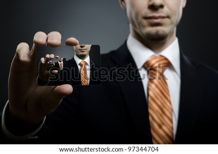 businessman in black costume and orange necktie reach out on camera and show credit card , close up - stock photo