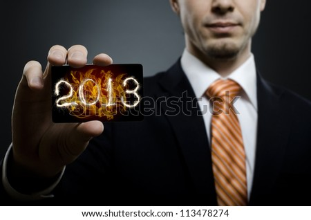 businessman in black costume and orange necktie reach out on camera and show credit card with date 2013, close up - stock photo