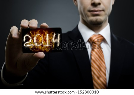 businessman in black costume and orange necktie reach out on camera and show credit card with date 2014, close up