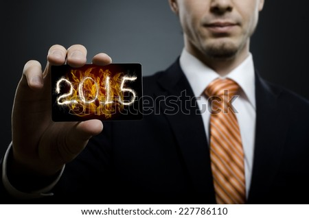 businessman in black costume and orange necktie reach out on camera and show credit card with date 2015, close up