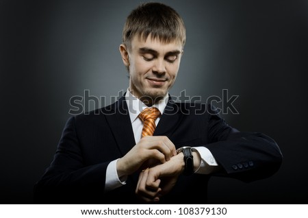 businessman in black costume wind clock (wristwatch) on hand,  close up