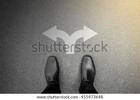 Businessman in black shoes standing at the crossroad making decision - darkness or brightness representing good or bad, right or wrong, success or failure