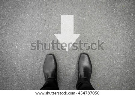 Businessman in black shoes standing on asphalt concrete road and direction sign backward. Wrong way and have to go back. - stock photo