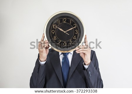 Businessman in black suit and white shirt with clock instead of head isolated over white background - stock photo