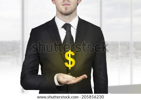 businessman in black suit holding golden dollar symbol in open hand