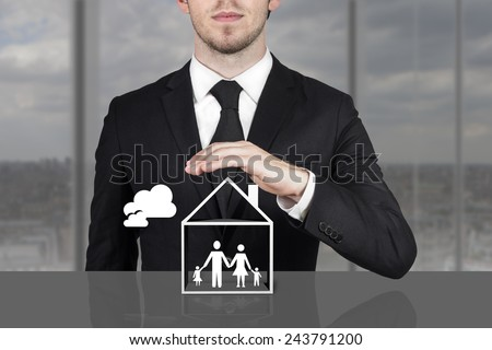 businessman in black suit holding protective hand above family home - stock photo