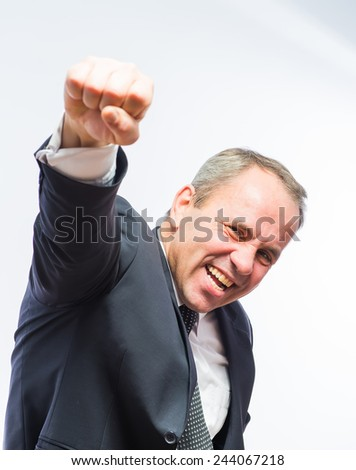 Businessman in black suit holding up his clenched fist - stock photo