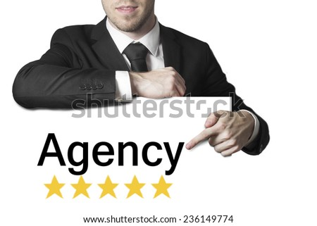 businessman in black suit pointing on sign agency - stock photo