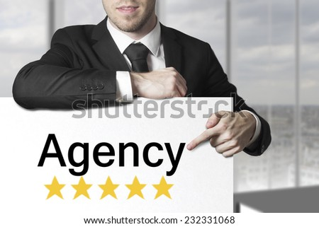 businessman in black suit pointing on sign agency golden star rating - stock photo