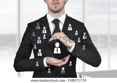 businessman in black suit protecting person chief and employees with hands - stock photo