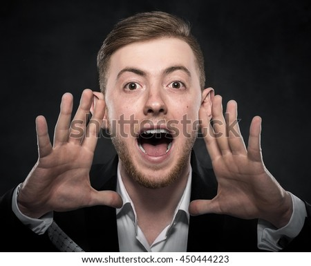 Businessman in black suit shouts lifting his hands up. on a dark background.