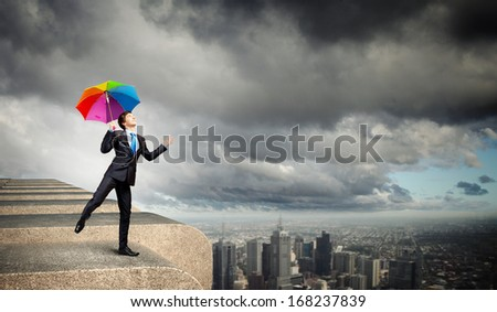 Businessman in black suit with umbrella atop of building
