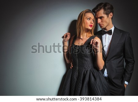 businessman in black with hand in pocket looks away behind woman with hands raised while looking at the man. couple is posing in gray studio background.