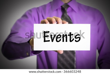 Businessman in blue shirt and gray tie shows a card with the inscription events. Man on a gray background. Selective focus. - stock photo