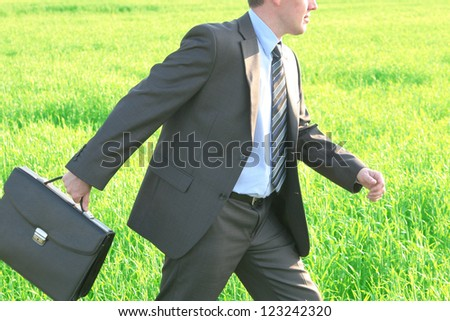 Businessman in blue shirt and tie going with crossed legs in grass field with confident look  Space for inscription