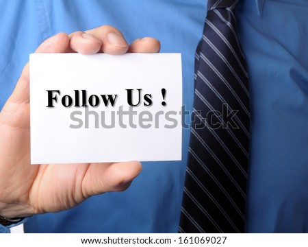 businessman in blue shirt and tie shows someone his business card with follow us