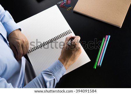 Businessman in blue shirt writing investment idea on book - stock photo