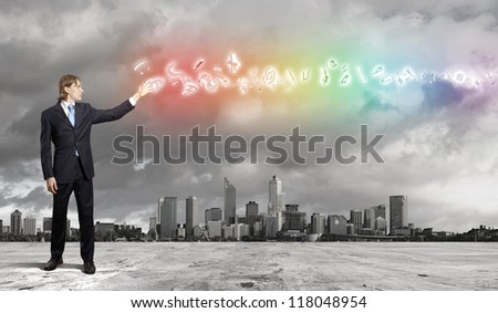 businessman in blue suit standing and juggling business symbols - stock photo