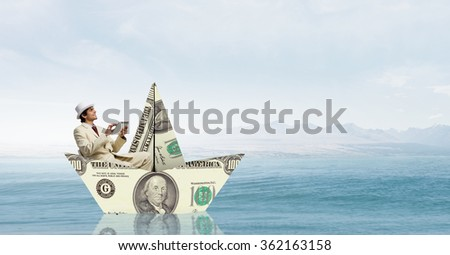 Businessman in boat made of dollar banknote - stock photo