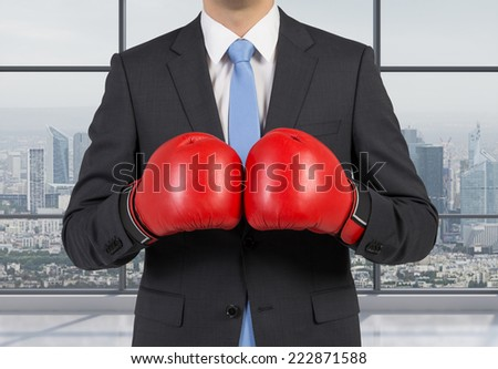 Businessman in boxing gloves, city view background. - stock photo