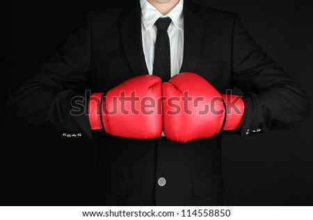 businessman in boxing gloves isolated on black