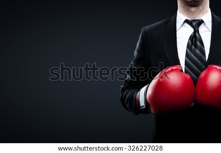 businessman in boxing gloves isolated on black background - stock photo