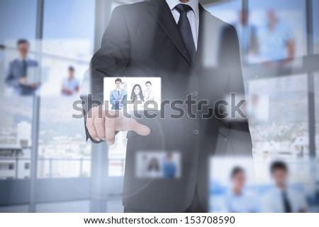 Businessman in bright office presenting digital interface showing coworkers