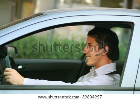 Businessman in car with hands-free blue-tooth