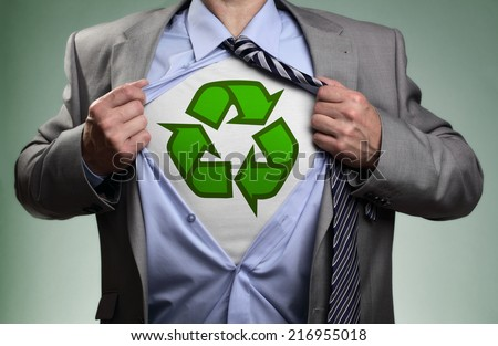 Businessman in classic superman pose tearing his shirt open to reveal t shirt with recycling symbol concept for recycling and environmental conservation - stock photo