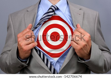 Businessman in classic superman pose tearing his shirt open to reveal target symbol on chest concept for human resources and recruitment - stock photo
