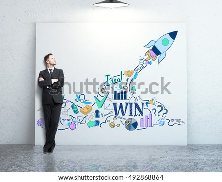 Businessman in concrete room leaning on whiteboard with creative rocket ship and business icons sketch. Start up concept